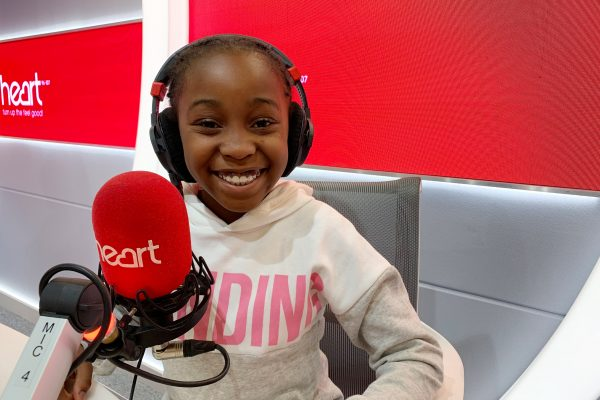 Child sitting in the Heart radio studio in front of a mic and with headphones on